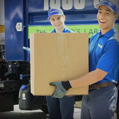 Two truck team members holding boxes